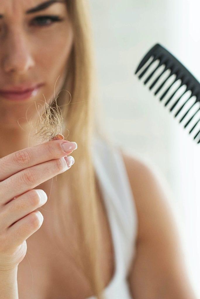 Frau mit Haarausfall und Kamm
