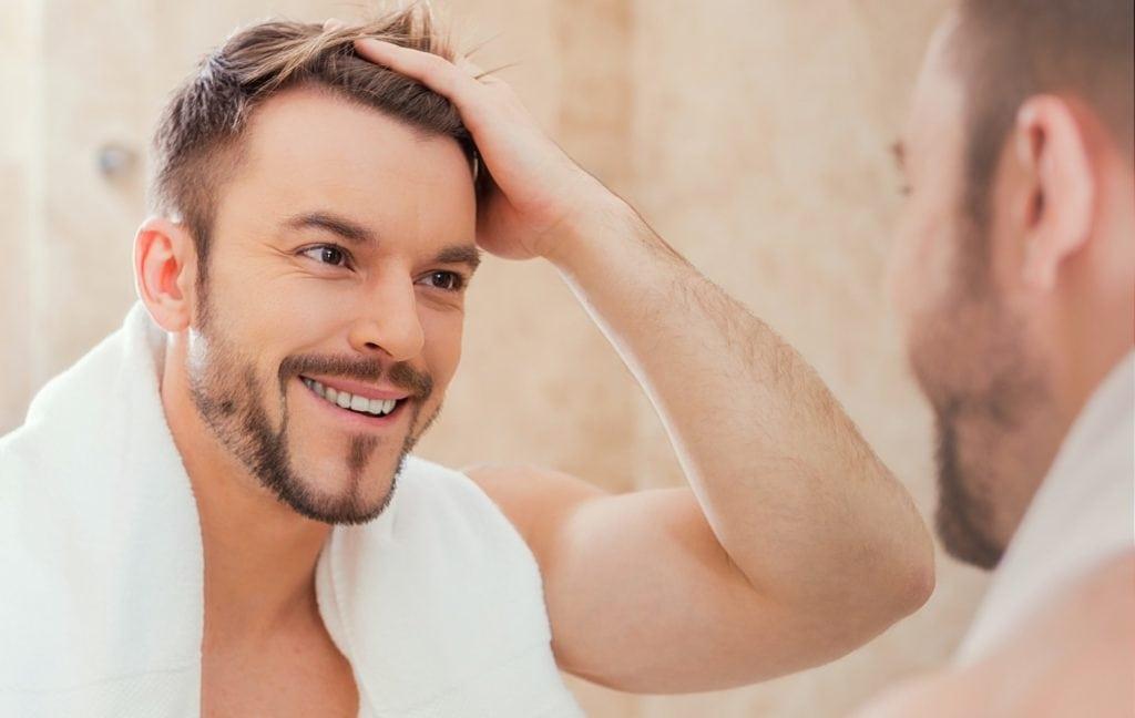 Glücklicher Mann greift sich mit Hand in sein volles Haar