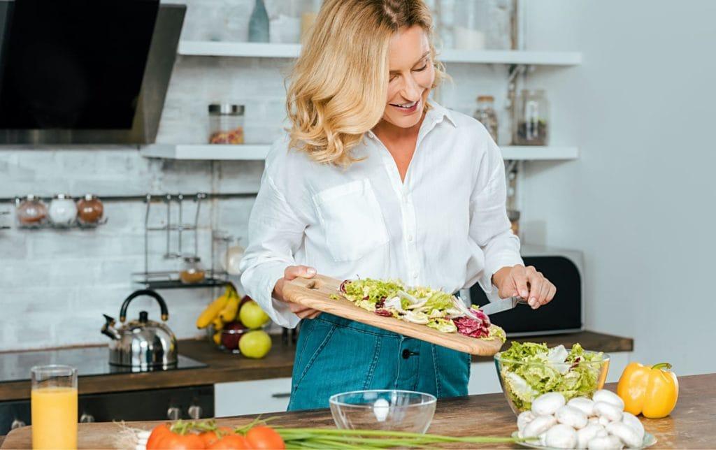 Blonde Frau schneidet in Küche Gemüse auf Holzbrett