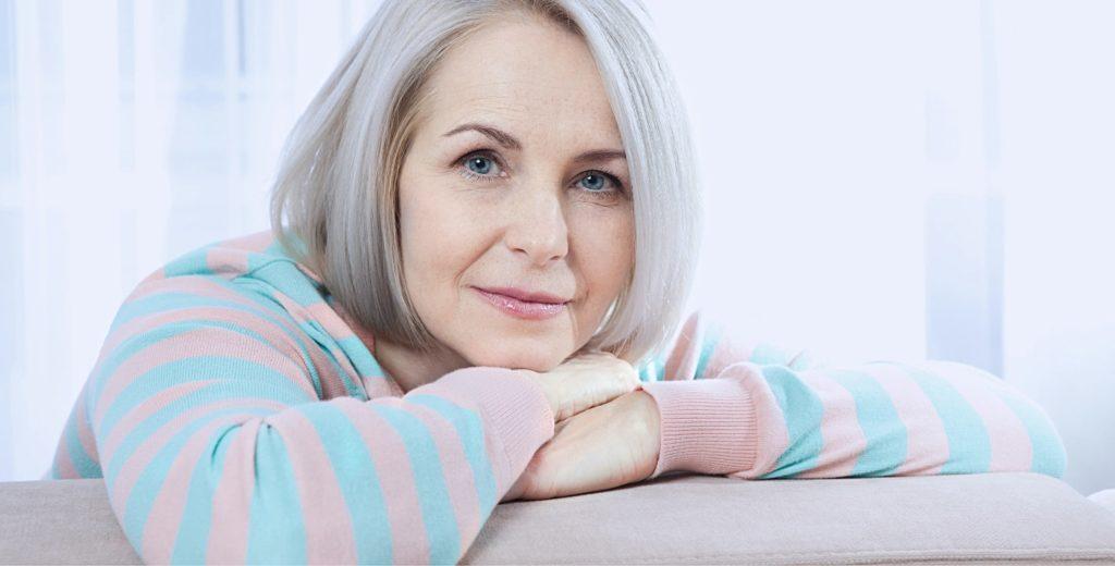 Frau mit Kopf auf den Armen aufgelegt auf einem Sofa