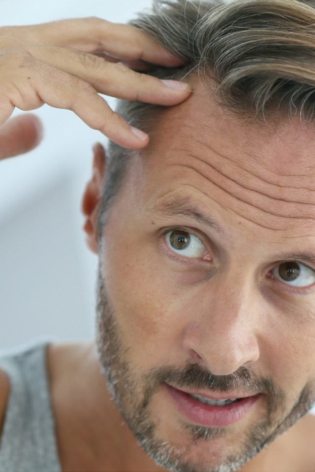 Mann mit Geheimratsecken mit kritischem Blick