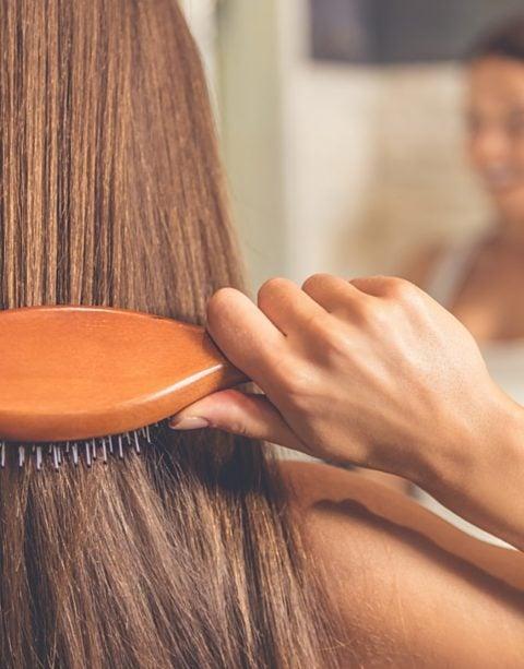 Frau mit vollem Haar bürstet sich vor Spiegel