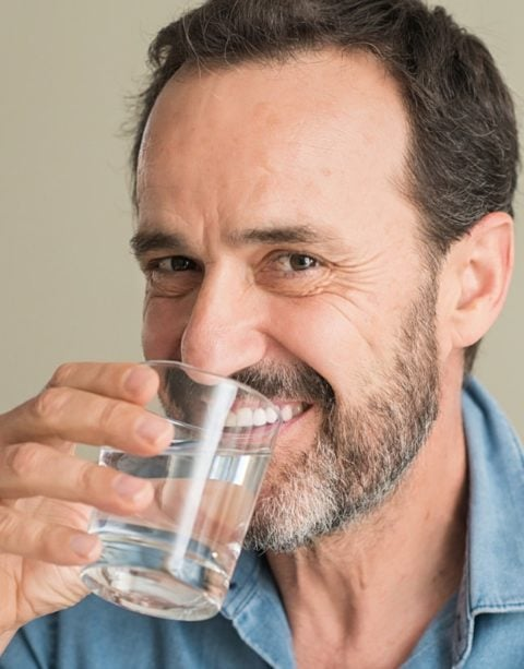 Lächelnder Mann trinkt Glas Wasser